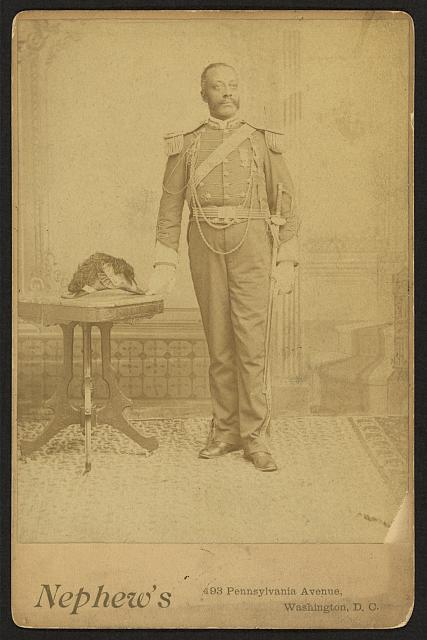 [African American soldier, full-length portrait, wearing GAR medal, standing next to table]