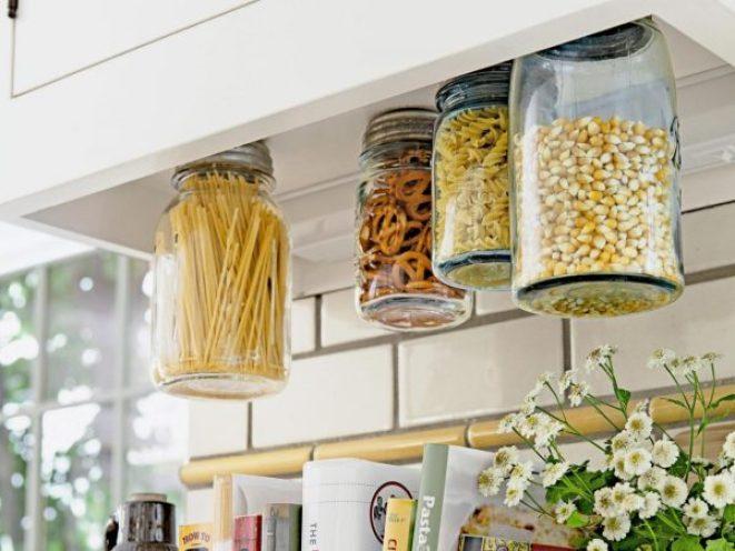 4 mason jars screwed under a kitchen cabinet are storing pasta, pretzels, and popcorn kernels