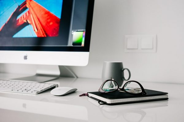 clean home office desk with a notebook, glasses, coffee mug, and imac on top
