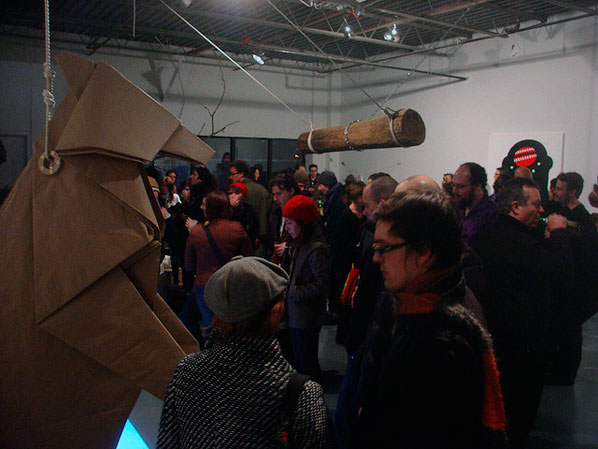 The life-size paper bear in situ during a gallery opening.