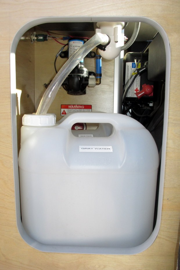 The gray and potable water tanks below the sink.