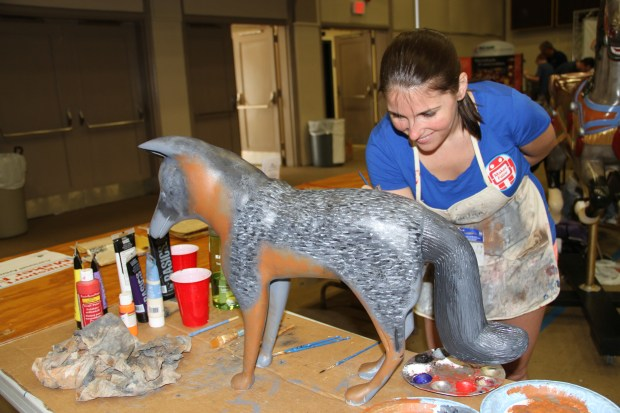 Jaclyn Bowen paints one of the many carved wooden characters that will be part of the active working carousel that will be operating in Kingsport next spring.