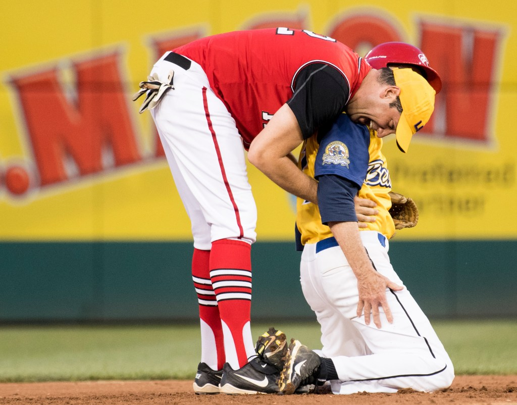 UNITED STATES - JUNE 15: Democrats' shortstop Rep. Tim Ryan, D-Ohio, gives Rep. Jack Bergman, R-Mich., a hug after a play at second base during the annual Congressional Baseball Game at Nationals Park in Washington on Thursday, June 15, 2017. (Photo By Bill Clark/CQ Roll Call)