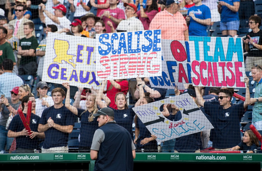 UNITED STATES - JUNE 15: A member of the Capitol Police security force guards the field as fans wave signs in support of House Majority Whip Steve Scales, R-La., during the annual Congressional Baseball Game at Nationals Park in Washington on Thursday, June 15, 2017. Scales was shot during baseball practice the previous day. (Photo By Bill Clark/CQ Roll Call)