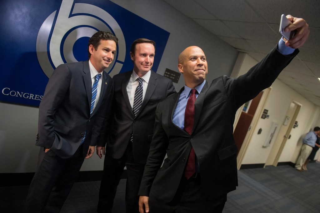 Democratic Sens. Brian Schatz of Hawaii, Chris Murphy of Connecticut and Cory Booker of New Jersey take a selfie before a meeting with CBO Director Keith Hall in Ford Building where they asked for a copy of the Republicans' health care bill. (Tom Williams/CQ Roll Call)