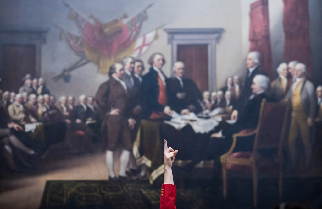 UNITED STATES - JUNE 28: A Capitol Visitor Center tour guide points up in front of John Trumbull's