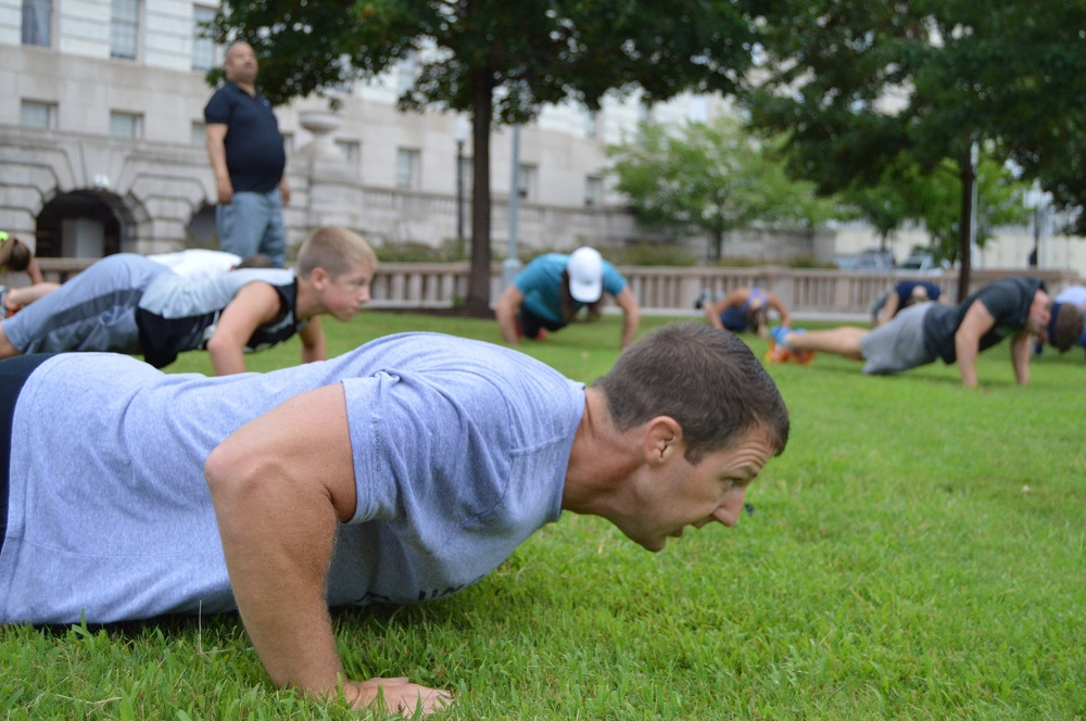Markwayne Mullin (R-OK) does a push-up while leading the Congressional Men's Health Caucus Workout. (Ana Fadich, VP of Men's Health Network)