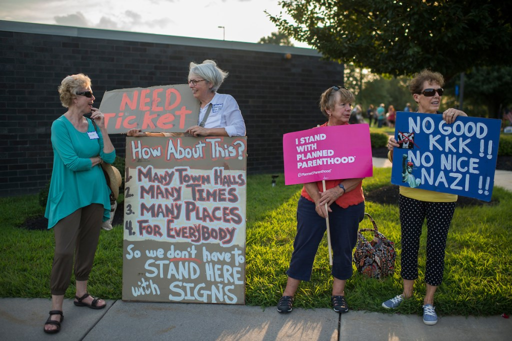 Demonstrators who did not obtain a lottery ticket for the town hall of Rep. Brian Fitzpatrick, R-Pa., protest outside the meeting. (Tom Williams/CQ Roll Call)