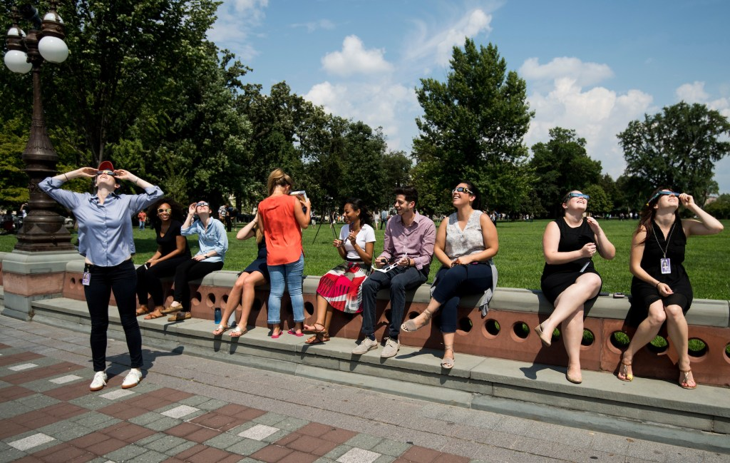 UNITED STATES - AUGUST 21: Staffers and tourists sit across from the east front of the U.S. Capitol during the partial solar eclipse on Monday, Aug. 21, 2017. (Photo By Bill Clark/CQ Roll Call)