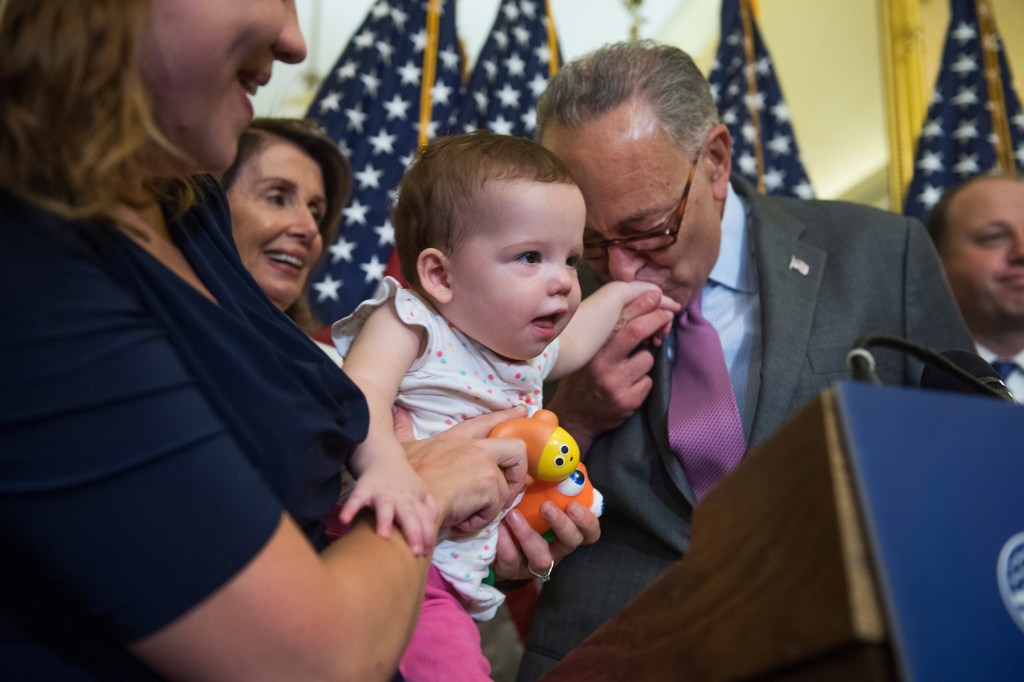 Senate Minority Leader Charles E. Schumer, D-N.Y., greets Alice Treadway, 1, as House Minority Leader Nancy Pelosi, D-Calif., and Alice's mother Joan Shipps, look on, during a news conference Thursday in the Capitol on the Child Care for Working Families Act, which focuses on affordable early learning and care. (Tom Williams/CQ Roll Call)