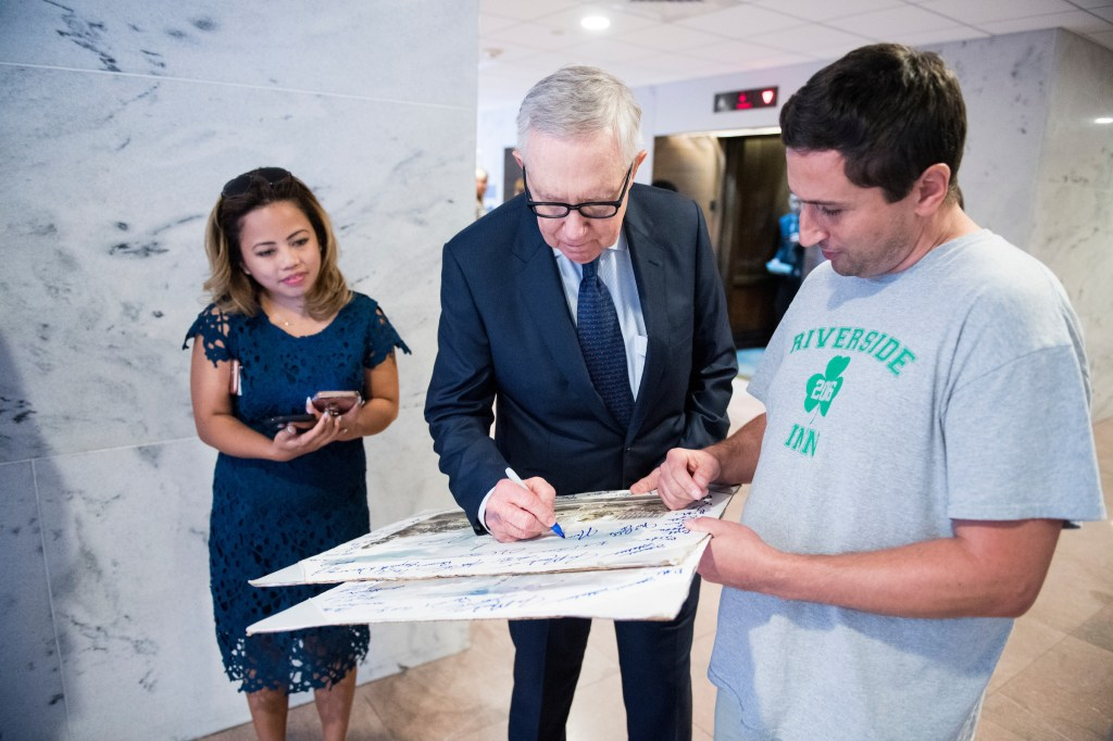 UNITED STATES - SEPTEMBER 14: Former Senate Majority Leader Harry Reid, D-Nev., stops to autograph a picture of the Capitol as he leaves the Hart Senate Office Building on Thursday, Sept. 14, 2017. (Photo By Bill Clark/CQ Roll Call)