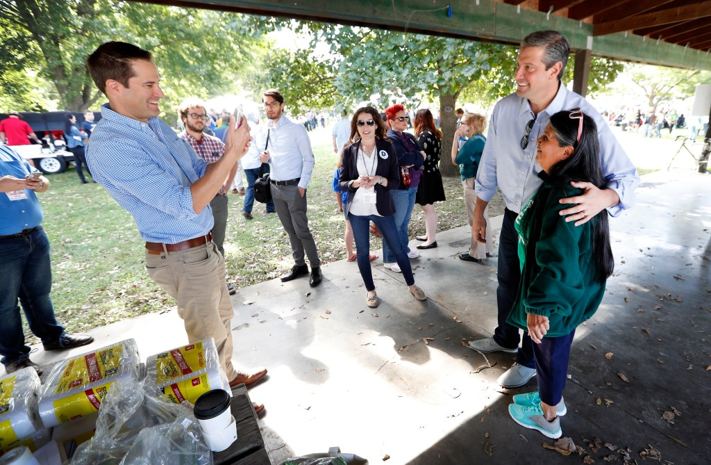 U.S. Rep. Seth Moulton, D-Mass., left, takes a photo of U.S. Rep. Tim Ryan, D-Ohio, with Paula Martinez, of Carlisle, Iowa, during the Polk County Democrats Steak Fry, Saturday, Sept. 30, 2017, in Des Moines, Iowa. (AP Photo/Charlie Neibergall)