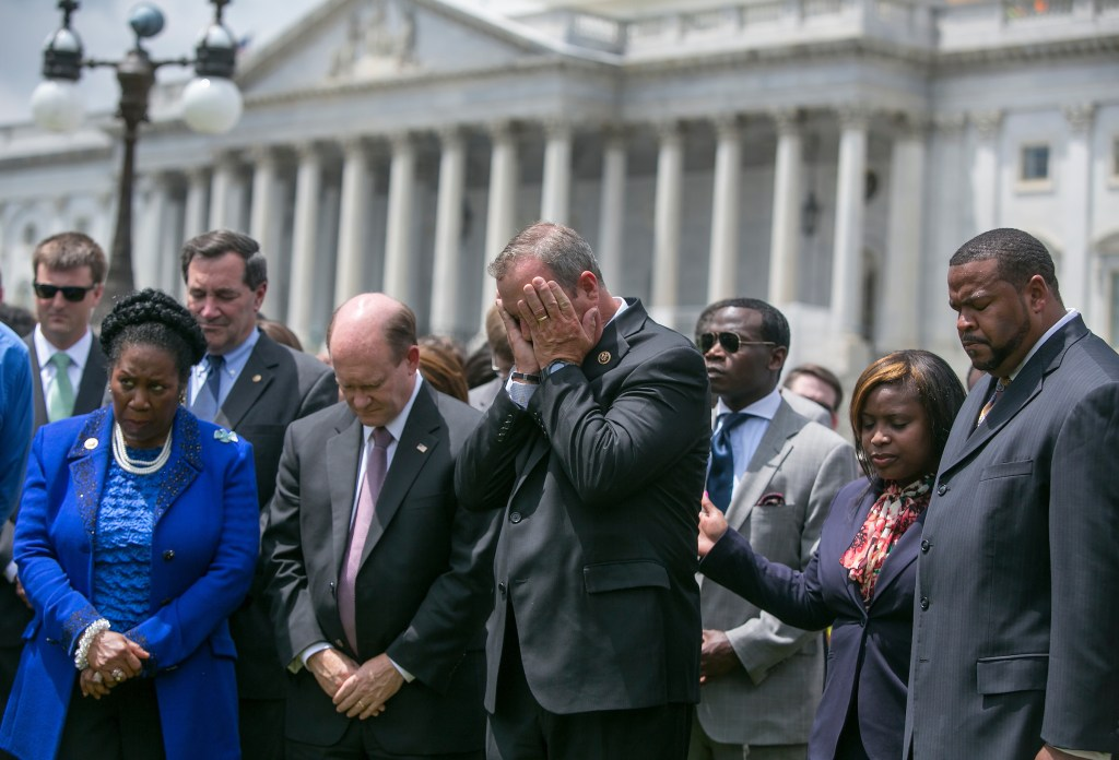 UNITED STATES - JUNE 18 - Rep. Jeff Duncan, R-S.C., center, holds his face as he stands besides Rep. Sheila Jackson Lee, D-Texas, left, and Sen. Chris Coons, D-Del., during a prayer vigil for victims of the Charleston shooting, outside of the U.S. Capitol on Thursday, June 18, 2015. (Photo By Al Drago/CQ Roll Call)