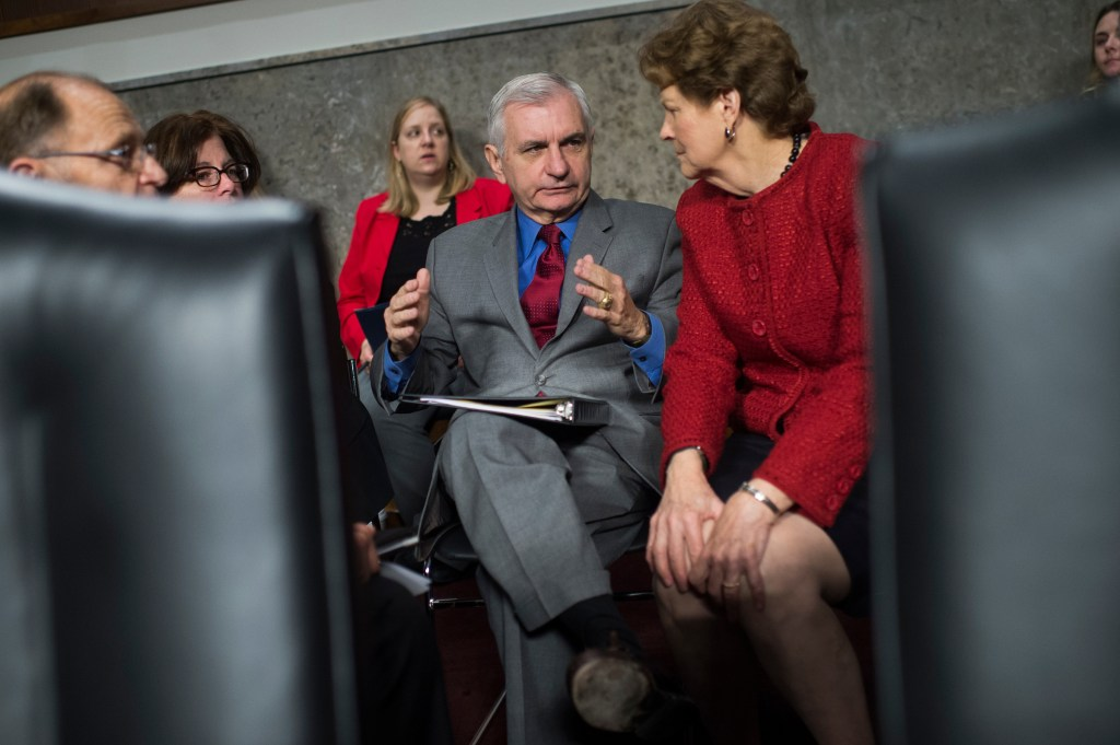 UNITED STATES - NOVEMBER 07: Sen. Jack Reed, D-R.I., ranking member, and Jeanne Shaheen, D-N.H., right, talk with staff before a Senate Armed Services Committee hearing in Dirksen Building on a variety of nominations on November 7, 2017. (Photo By Tom Williams/CQ Roll Call)