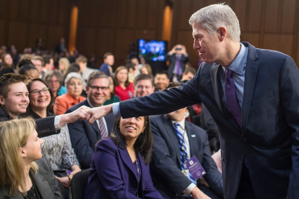 UNITED STATES - MARCH 21: Supreme Court Justice nominee Neil Gorsuch fist bumps his nephew, Jack, on the second day of his Senate Judiciary Committee confirmation hearing in Hart Building, March 21, 2017.(Photo By Tom Williams/CQ Roll Call)