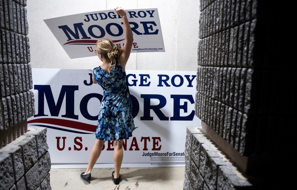 UNITED STATES - AUGUST 4: Judge Roy Moore campaign worker Maggie Ford collects campaign signs after the U.S. Senate candidate forum held by the Shelby County Republican Party in Pelham, Ala., on Friday, Aug. 4, 2017. Moore is running in the special election to fill the seat vacated by Attorney General Jeff Sessions. (Photo By Bill Clark/CQ Roll Call)
