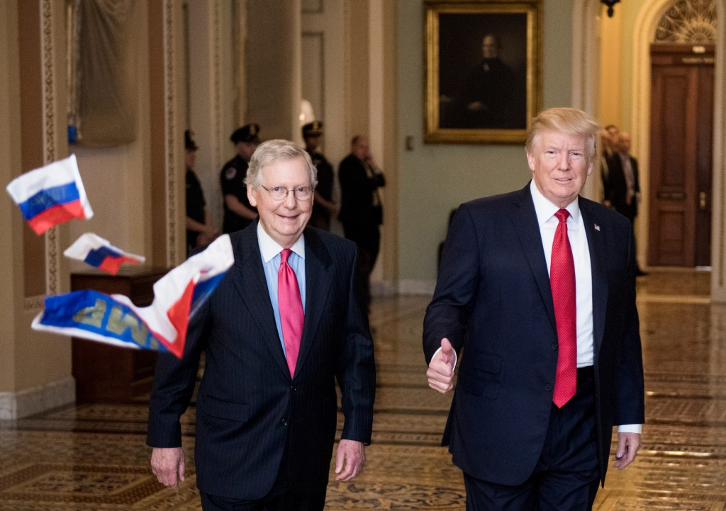 UNITED STATES - OCTOBER 24: A protester throws Russian flags towards Senate Majority Leader Mitch McConnell, R-Ky., and President Donald Trump as they arrive for the Senate Republicans' policy lunch in the Capitol on Tuesday, Oct. 24, 2017. (Photo By Bill Clark/CQ Roll Call)