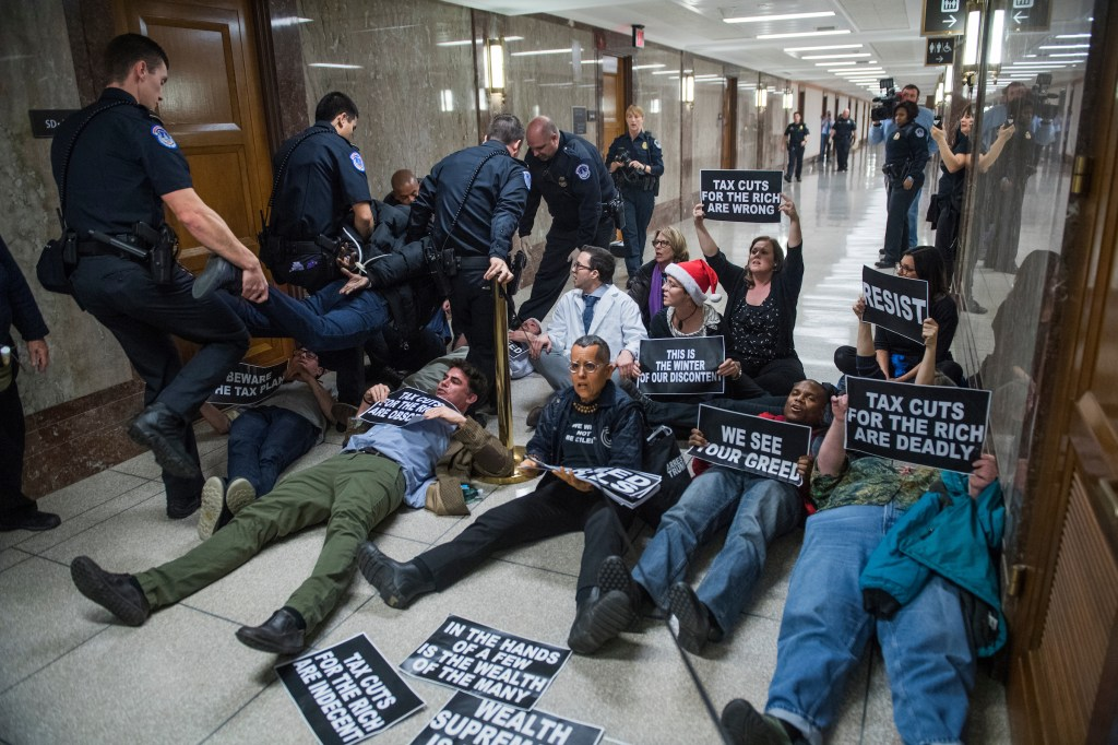 UNITED STATES - NOVEMBER 28: Protesters disrupt the Senate Budget Committee markup of the tax reform bill in Dirksen Building on November 28, 2017. (Photo By Tom Williams/CQ Roll Call)
