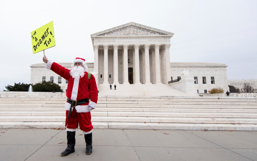 UNITED STATES - DECEMBER 6: Francisco Gutierrez,of Middletown, N.Y., dresses as Santa Claus in front of the Supreme Court building as immigration protests erupt around the Capitol on Wednesday, Dec. 6, 2017. The protest was held to call on Congress to find a legislative fix for the legal status of people brought into the country illegally as children. (Photo By Bill Clark/CQ Roll Call)