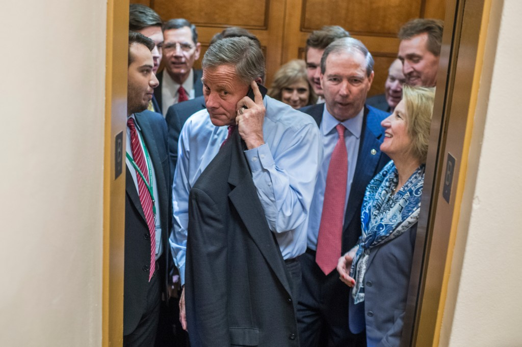 UNITED STATES - DECEMBER 06: Sens. Richard Burr, R-N.C., on phone, Shelley Moore Capito, R-W.Va., right, and other senators are seen in the senate subway before a vote in the Capitol on December 6, 2017. (Photo By Tom Williams/CQ Roll Call)