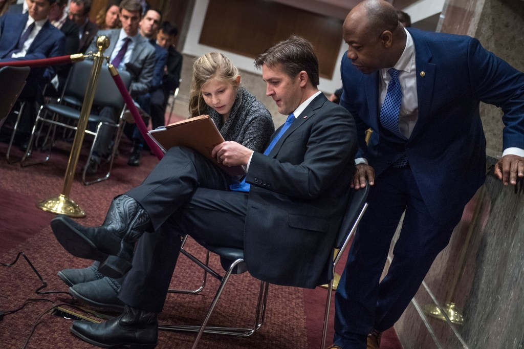 Sen. Ben Sasse, R-Neb., helps his daughter Alexandra, 14, with algebra homework as Sen. Tim Scott, R-S.C., looks on, during a Senate Armed Services Committee hearing in Dirksen Building titled