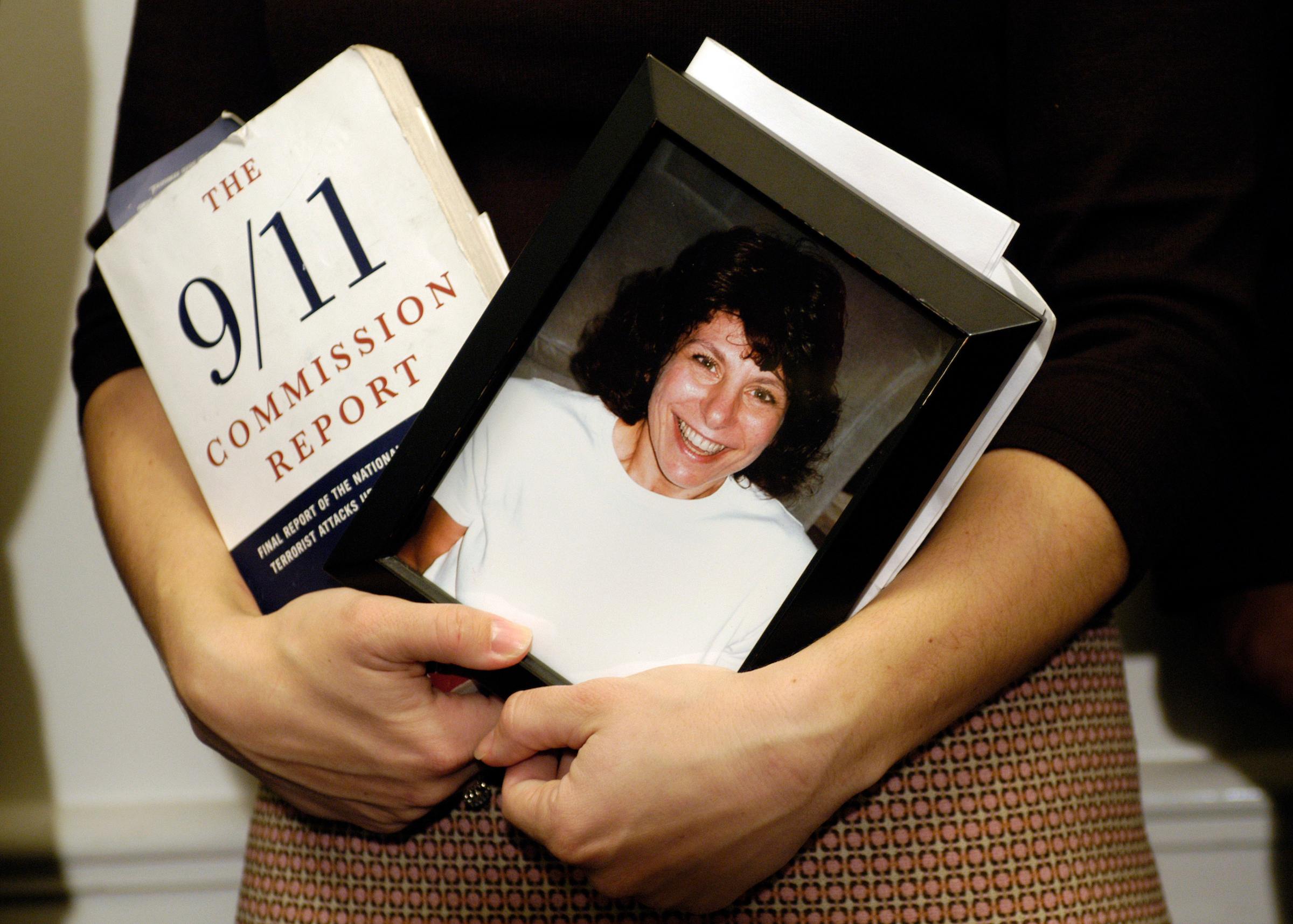Carie LeMack, whose mother died in 9/11,held a copy of the 9/11 commssion report and a picture of her mother today at press conference urging Congressial committee reform recommended by the 9/11 commission.