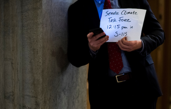 UNITED STATES - MARCH 13: A Senate staffer holds a sign by the Senate carriage entrance to guide attendees to the Senate Climate Task Force meeting in the Capitol on Tuesday, March 131, 2018. (Photo By Bill Clark/CQ Roll Call)