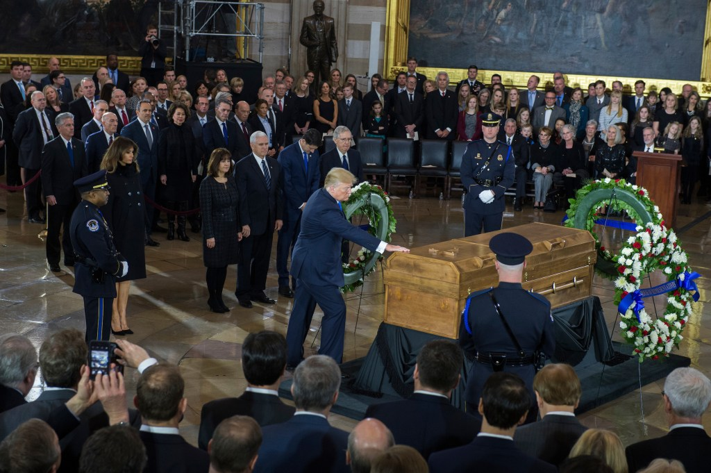 UNITED STATES - FEBRUARY 28: President Donald Trump touches the casket of the late Rev. Billy Graham as the body of Graham lies in honor in the Capitol Rotunda on February 28, 2018. (Photo By Tom Williams/CQ Roll Call)