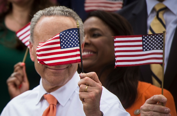 Senate Minority Leader Sen. Charles Schumer, D-NY, waves an American flag at the conclusion of Monday afternoon's 'A Better Deal for Our Democracy' press conference hosted by House and Senate Democrats May 21, 2018. (Photo By Sarah Silbiger/CQ Roll Call)