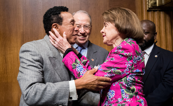 UNITED STATES - MAY 15: Recording artist Smokey Robinson, left, gives Sen. Dianne Feinstein, D-Calif., a kiss as Sen. Chuck Grassley, R-Iowa, looks on before the start of the Senate Judiciary Committee hearing on