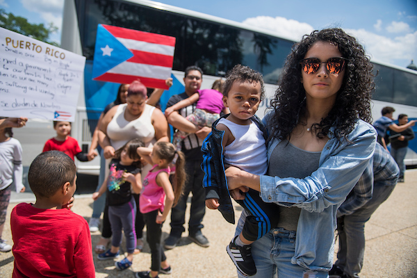 UNITED STATES - JUNE 6: Analee Dalmau, and her son Mathais, 16 months, along with other Puerto Ricans who were displaced by Hurricane Maria, arrive in buses from western Massachusetts on First St., NE, on June 6, 2018. They came to urge members of Congress to enact the Disaster Housing Assistance Program (DHAP) because FEMA has not done so. (Photo By Tom Williams/CQ Roll Call)