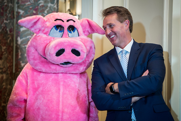 UNITED STATES – July 18: Sen. Jeff Flake, R-Ariz., laughs with a staffer dressed as a pig during the 2018 Congressional Pig Book launch event hosted by Citizens Against Government Waste Wednesday July 18, 2018. (Photo By Sarah Silbiger/CQ Roll Call)