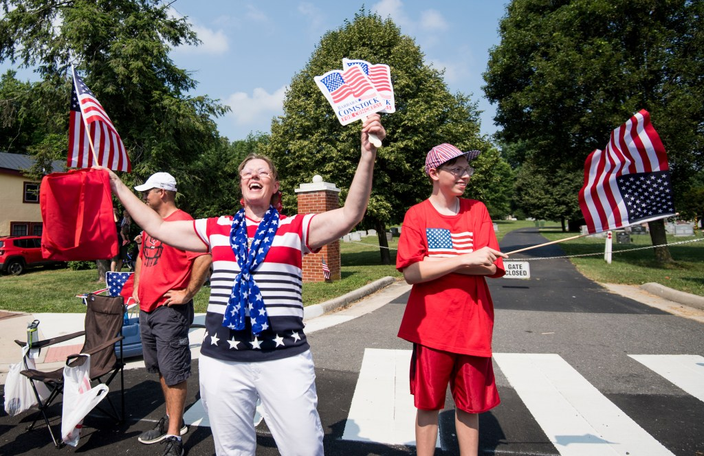 A supporter of Rep. Barbara Comstock, R-Va., holds up a flag and Comstock fans at the Leesburg Independence Day Parade in Leesburg, Va., on July 4, 2018. Comstock facing a Democrat Jennifer Wexton for Virginia's 10th Congressional district seat. (Photo By Bill Clark/CQ Roll Call)