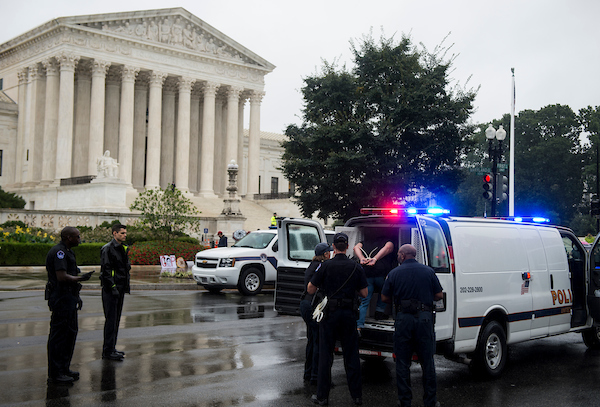 A woman is loaded into a police van after being arrested for sitting in on First Street outside of the Supreme Court as high court nominee Brett Kavanaugh testifies before the Senate Judiciary Committee. (Sarah Silbiger/CQ Roll Call)