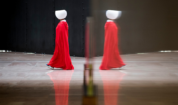 One of a dozen protesters dressed in The Handmaid's Tale costumes walks in a circle in the atrium of the Hart Senate Office Building during the confirmation hearing of Brett Kavanaugh to be Associate Justice of the Supreme Court in the Senate Judiciary Committee on Tuesday morning, Sept. 4, 2018. (Bill Clark/CQ Roll Call)