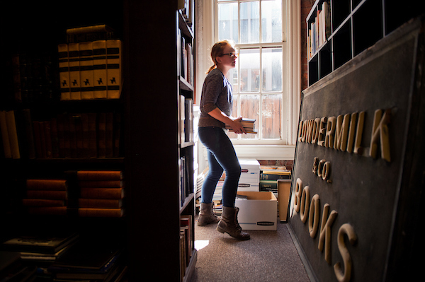 Lori Grisham, manager of Riverby Books on East Capitol St., SE, stacks books while setting up the store for it's reopening this month, October 15, 2015. (Tom Williams/CQ Roll Call)