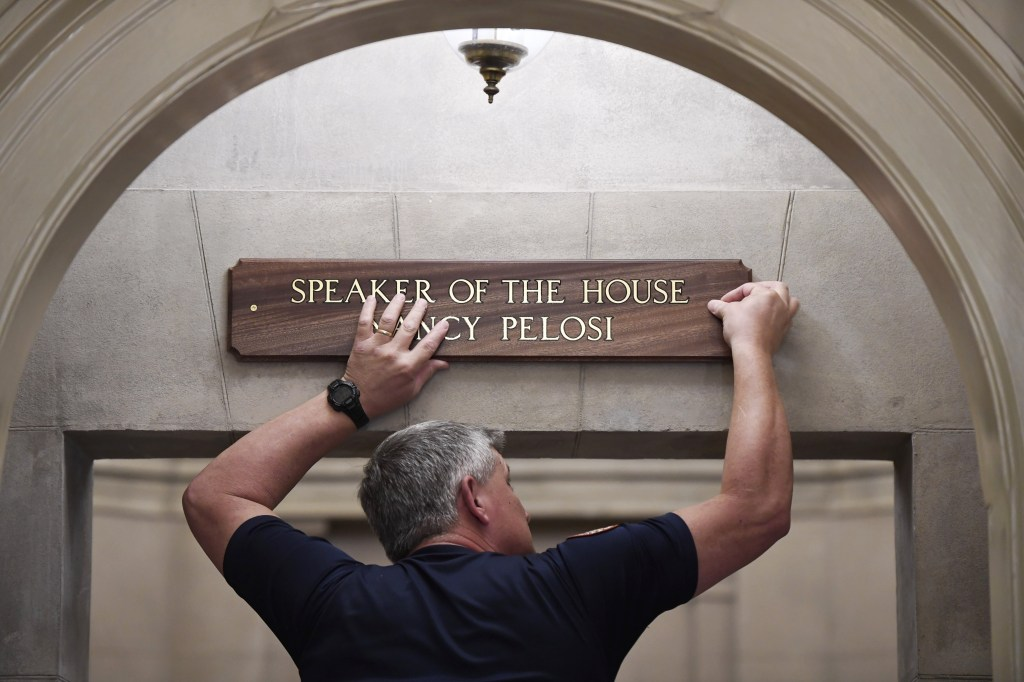 A member of the U.S. Capitol staff hangs a sign over the office for Speaker Nancy Pelosi D-Calif. following her election Thursday. (Bill Clark/CQ Roll Call)