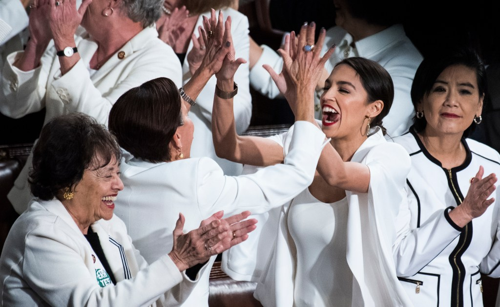 UNITED STATES - FEBRUARY 05: Reps. Alexandria Ocasio-Cortez, D-N.Y., right, high fives Nydia Velazquez, D-N.Y., as Democratic members celebrate in the House Chamber as President Donald Trump recognized their achievement of electing a record number of women to Congress, during the State of the Union address on Tuesday, February 5, 2019. (Photo By Tom Williams/CQ Roll Call)