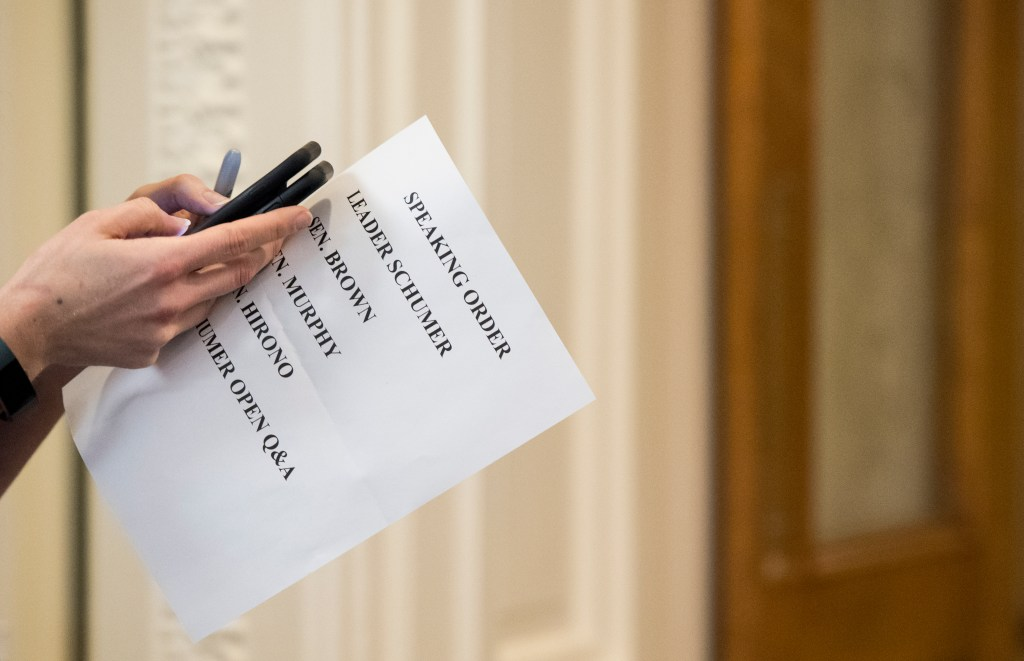 UNITED STATES - MARCH 5: A Senate staffer holds a sheet listing the speaking order for the press conference with Senate Minority Leader Chuck Schumer, D-N.Y., Sen. Sherrod Brown, D-Ohio, Sen. Chris Murphy, D-Conn., and Sen. Mazie Hirono, D-Hawaii, on the nomination of Chad Readler, to be U.S. Circuit Judge for the Sixth Circuit, on Tuesday, March 5, 2019. (Photo By Bill Clark/CQ Roll Call)