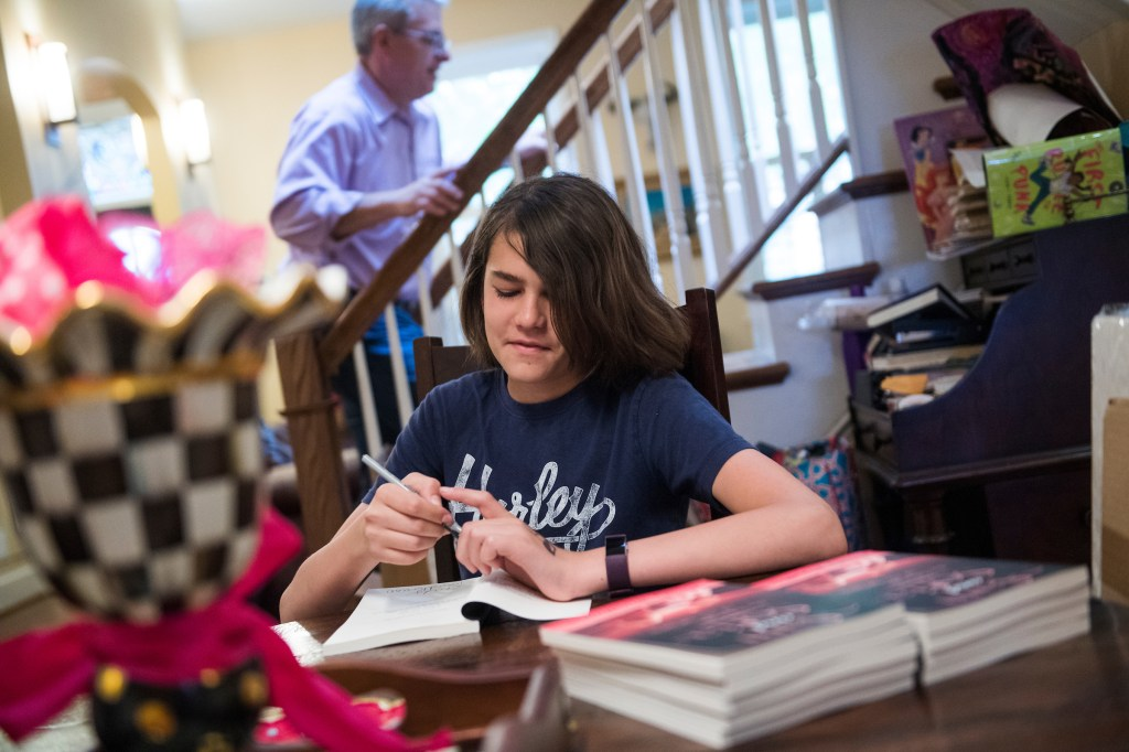 """Brady signs copies of his self-published book, """"Sam and Sofia: The Magic of the Stars,"""" in his Capitol Hill home on April 24. (Tom Williams/CQ Roll Call)"""