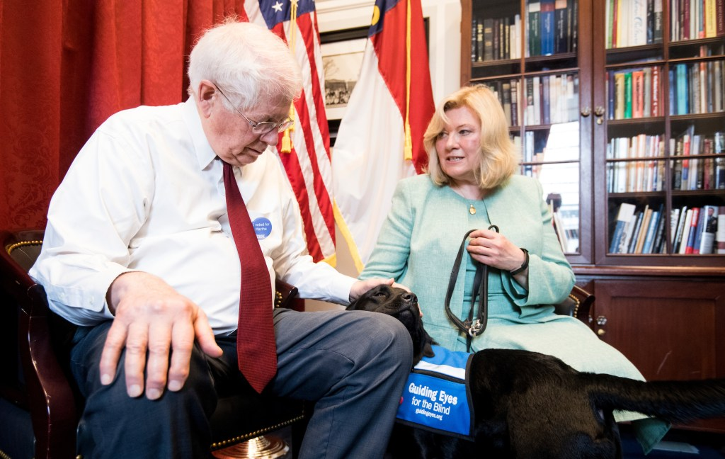 UNITED STATES - MAY 1: Volunteer puppy raiser Lorraine Trapani speaks with Rep. David Price, D-N.C., as he pets Kate, a 14 month old black labrador retriever in the Guiding Eyes for the Blind training program, in his office on Wednesday, May 1, 2019. Kate is wearing a