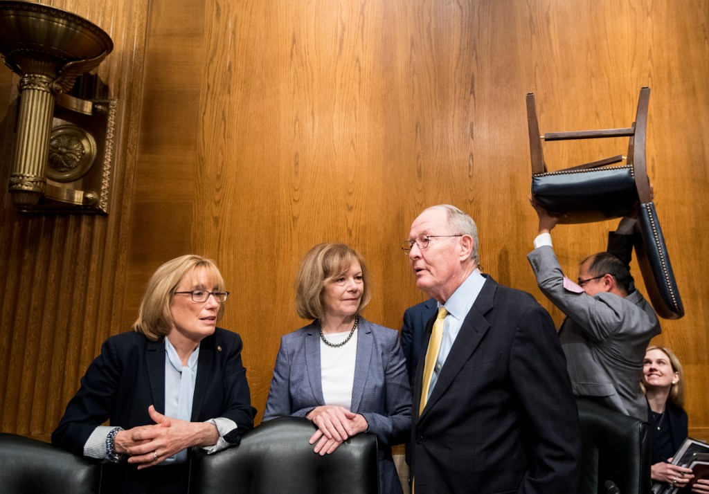 UNITED STATES - JUNE 18: From left, Sen. Maggie Hassan, D-N.H., Sen. Tina Smith, D-Minn., and chairman Sen. Lamar Alexander, R-Tenn., talk as a staffer carries a chair behind them before the start of the Senate Health, Education, Labor and Pensions Committee hearing on the
