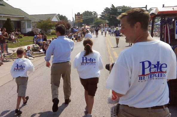 Campaigning in 2010 for Indiana state treasurer, Pete Buttigieg marches in a parade with campaign manager Jeff Harris, right, and Jamie and Erin Schronce. (Kathi Schronce photo)