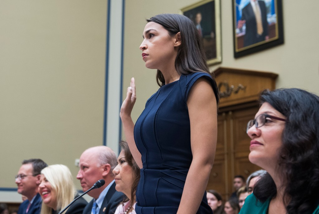 UNITED STATES - JULY 12: Rep. Alexandria Ocasio-Cortez, D-N.Y., is granted permission to be sworn in to a House Oversight and Reform Committee hearing in Rayburn Building where members of Congress testified about their trip to the border of the U.S. and Mexico on Friday, July 12, 2019. Seated from left are, Reps. Michael Cloud, R-Texas, Debbie Lesko, R-Ariz., Chip Roy, R-Texas, Veronica Escobar, D-Texas, Rashida Tlaib, D-Mich., and Ayanna Pressley, D-Mass. The hearing was titled