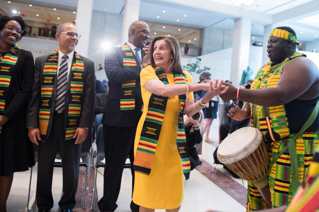 "UNITED STATES - SEPTEMBER 10: Speaker of the House Nancy Pelosi, D-Calif., dances with Adrian Somerville, Jr., a West African percussion performer, during a ceremony in the Capitol's Emancipation Hall to mark the ""the 400th anniversary of the first-recorded forced arrival of enslaved African people,"" on Tuesday, September 10, 2019. (Photo By Tom Williams/CQ Roll Call)"