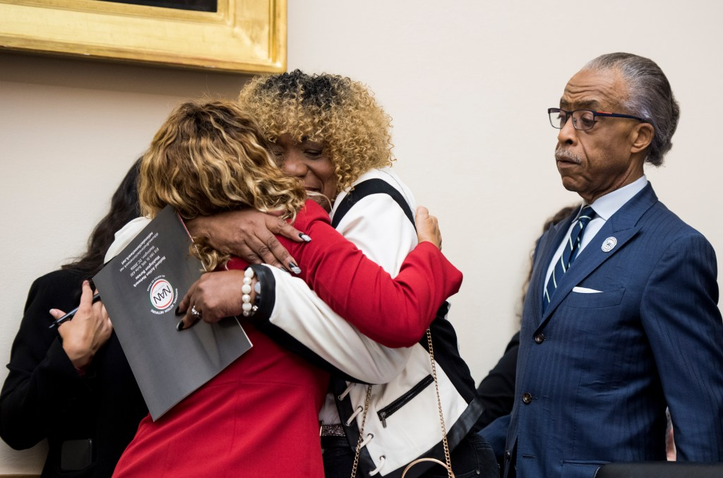 UNITED STATES - SEPTEMBER 19: From left, Rep. Lucy McBath, D-Ga., hugs Gwen Carr, mother of Eric Garner, as Reverend Al Sharpton looks on as Carr and Sharpton arrive to testify during the House Judiciary Committee hearing on policing practices on Thursday, Sept. 19, 2019. (Photo By Bill Clark/CQ Roll Call)