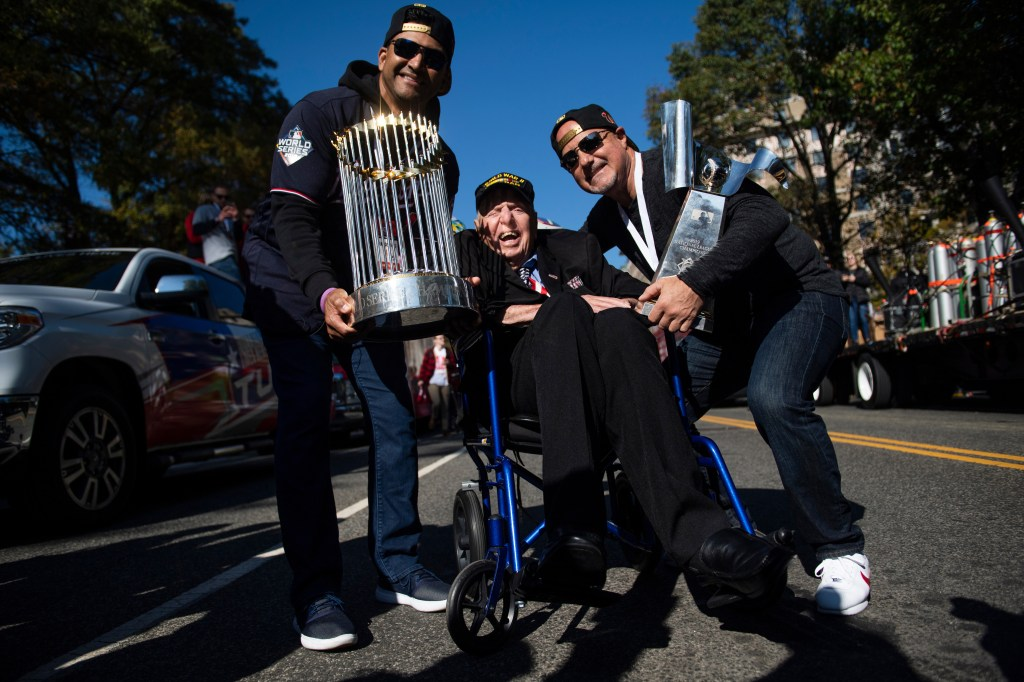UNITED STATES - NOVEMBER 02: Washington Nationals manager Dave Martinez, left, and general manager Mike Rizzo, pose with World War II veteran Sidney Walton, 100, on 15th St., NW, during a parade to celebrate the World Series champions on Saturday, November 2, 2019. (Photo By Tom Williams/CQ Roll Call)