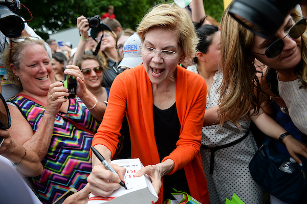 UNITED STATES - AUGUST 10: Democratic presidential candidate Sen. Elizabeth Warren, D-Mass., signs a copy of the Mueller Report for a fairgoer at the Iowa State Fair on Saturday August 10, 2019. (Photo by Caroline Brehman/CQ Roll Call)