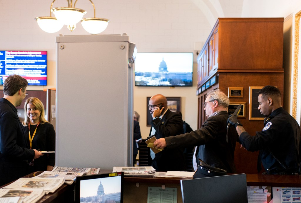 UNITED STATES - JANUARY 21: A U.S. Capitol Police officer checks a reporter for electronic devices as he enters the Senate chamber to take his his seat in the press section on Tuesday, Jan. 21, 2020. A magnetometer was set up in the Senate Press Gallery for the Senate impeachment trial. (Photo By Bill Clark/CQ Roll Call)