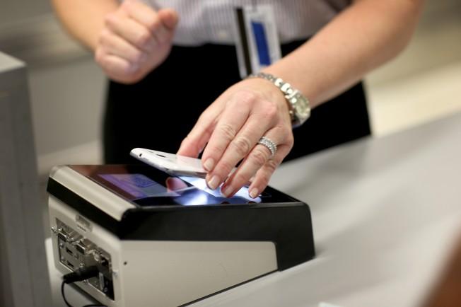 美國海關及邊境保護局職員展示如何使用「手機護照」應用程式快速通關,這項服務即將在全美國際機場啟用。(Getty Images)</p><br /><br /> <p>